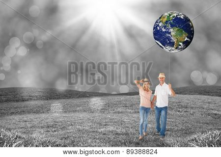 Happy couple walking holding hands against field with glowing sky