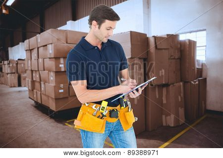 Carpenter writing on clipboard over white background against cardboard boxes in warehouse