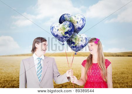 Smiling geeky couple holding red balloons against bright brown landscape
