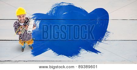 Frustrated handyman holding various tools against painted blue wooden planks