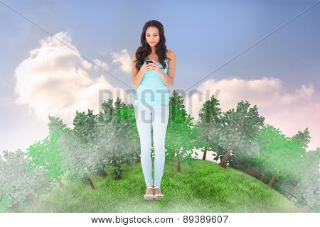 Casual brunette sending a text against beautiful blue cloudy sky