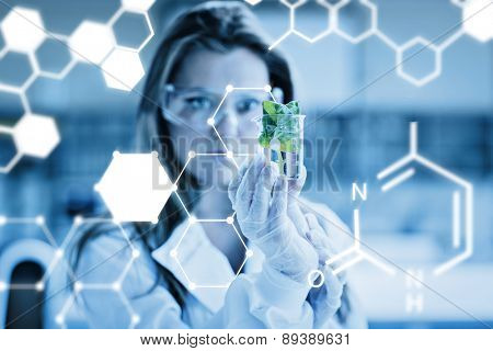 Science graphic against woman standing at the laboratory holding a glass with plant