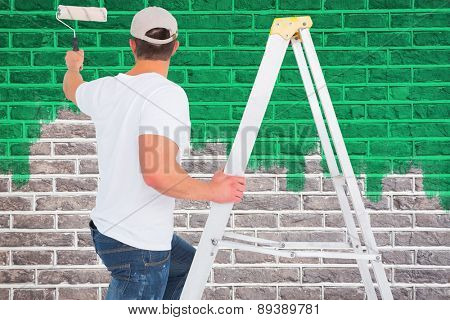 Handyman climbing ladder while using paint roller against red brick wall