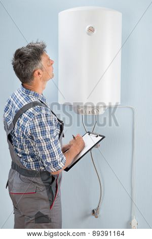 Male Plumber With Clipboard Looking At Electric Boiler