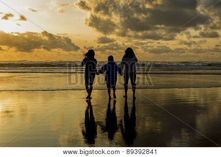 Family At The Beach At Sunset.