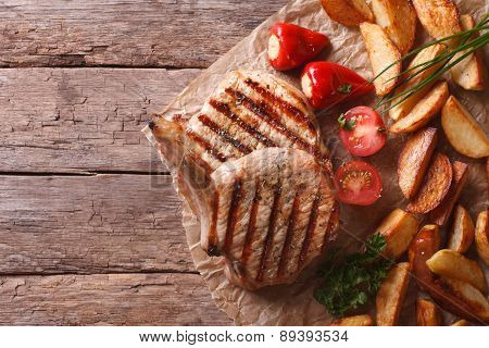 Grilled Pork Steak With Potatoes On Paper Top View Horizontal