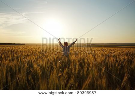 Woman Stands In A Field Of Ripe Wheat