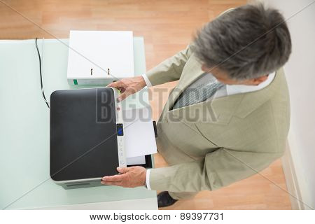 Mid-adult Businessman Using Photocopy Machine