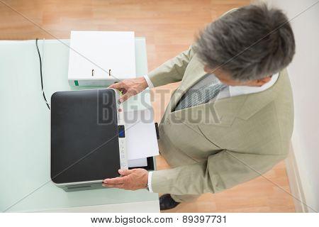 Mid-adult Businessman Using Photocopy Machine