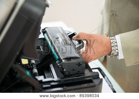 Businessman Fixing Cartridge In Photocopy Machine