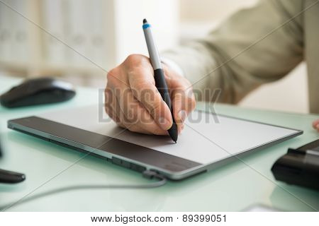 Businessman Writing On Graphic Tablet