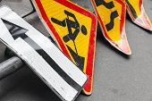 image of road construction  - Bright red and yellow roadsigns lay on the asphalt road - JPG