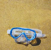 image of rubber mask  - close up of a diving mask on a golden beach - JPG