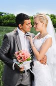 picture of married  - A married couple bride and groom about to kiss in sunshine on a beautiful waterfront city - JPG