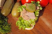 pic of baguette  - Slice of baguette with tuna fillet garnished with lettuce onion tomato and pickles on a wooden board - JPG