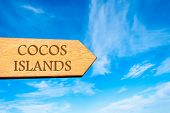 stock photo of coco  - Wooden arrow sign pointing destination COCOS ISLANDS against clear blue sky with copy space available - JPG