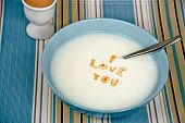 stock photo of cereal bowl  - Romantic message in cereal bowl with spoon and brown hard-boiled egg.