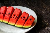 foto of watermelon slices  - slices of watermelon on wooden table with shadow - JPG