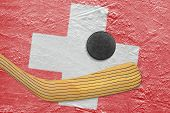 picture of hockey arena  - Hockey puck hockey stick and the image of the Swiss flag on the ice - JPG