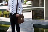 foto of coffee crop  - Cropped image of businessman with coffee and briefcase standing outdoors - JPG