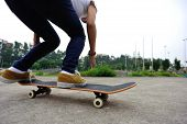 stock photo of skateboarding  - young asian skateboarder legs riding on skateboard outdoor - JPG