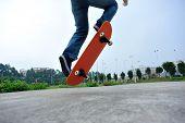 stock photo of skateboarding  - young skateboarder  legs doing skateboarding trick ollie outdoor - JPG