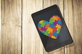 pic of autism  - Autism awareness heart against overhead of tablet on desk - JPG
