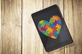 foto of autism  - Autism awareness heart against overhead of tablet on desk - JPG