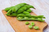 foto of bean-pod  - Fresh broad bean on wooden kitchen board - JPG