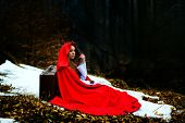 stock photo of cloak  - beautiful woman with red cloak in the woods - JPG