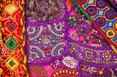 stock photo of flea  - Colorful ethnic Rajasthan cushion cover and belts with mirrors on flea market in India - JPG