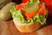 stock photo of baguette  - Slice of baguette with pollock fillet garnished with lettuce onion tomato and pickles on a wooden board - JPG