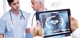 stock photo of x-files  - Man using tablet pc against doctors talking about a file - JPG