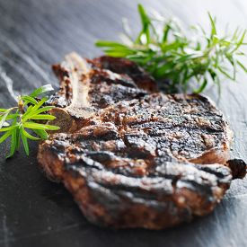 foto of slating  - grilled prime rib beef steak with rosemary on slate - JPG