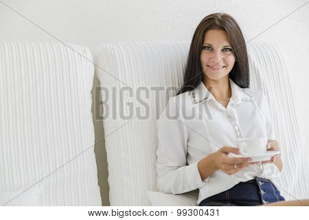 Beautiful Woman Sipping Coffee From A White Cup
