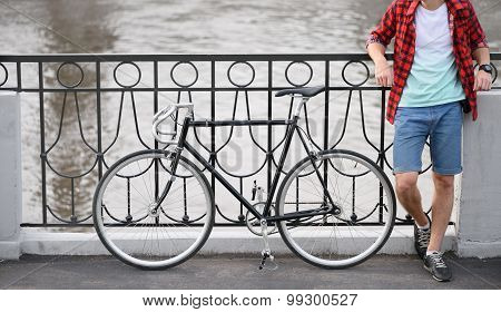 Hipster man with bicycle resting over quay