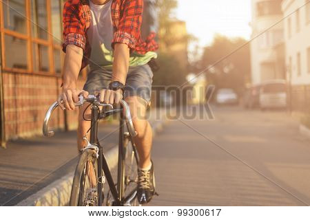 Close up hipster on bike in the city at sunset. Shot with sunflare and without face