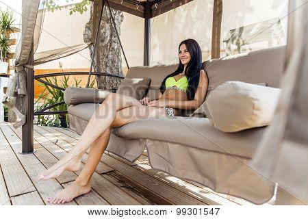 Beautiful Young Lady Shading Herself From Sun In A Big Swing