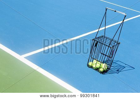 Tennis Court With A Ball Basket And Tennis Balls In It