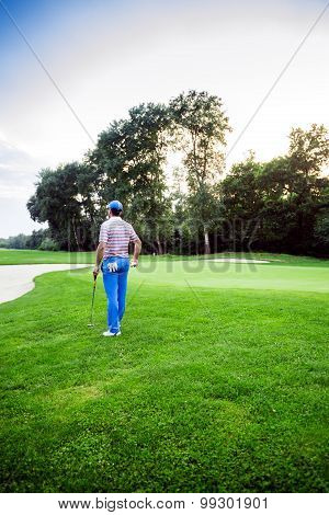 Beautiful Golfing Scenery With A Golfer Holding A Club