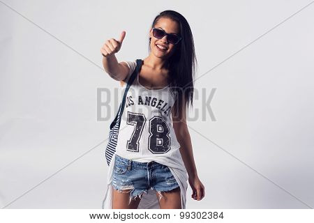 Young woman in sunglasses showing thumb up looking at camera. Portrait of trendy girl having fun sty