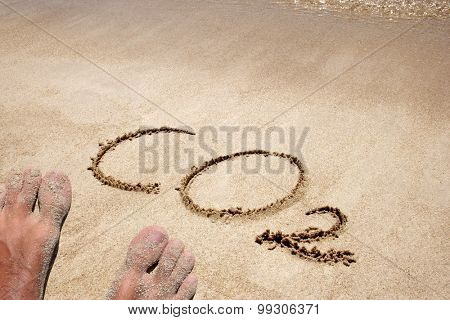 Concept or conceptual CO2 text hand written in sand on a beach on an exotic island background with feet for summer