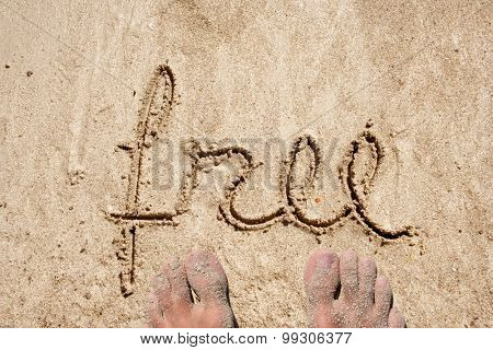 Conceptual free text hand written in sand on a beach on an exotic island background with feet