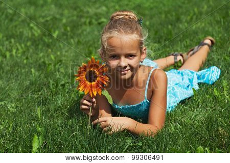 Little girl laying on the summer grass with a flower - copy space