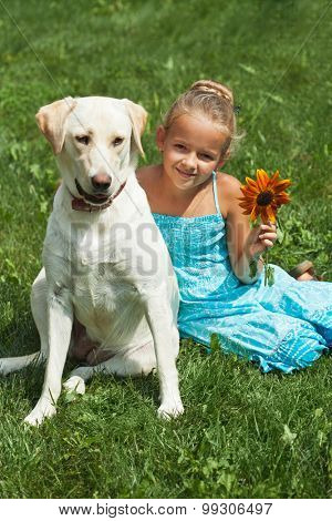Young girl sitting in the grass with her labrador dog