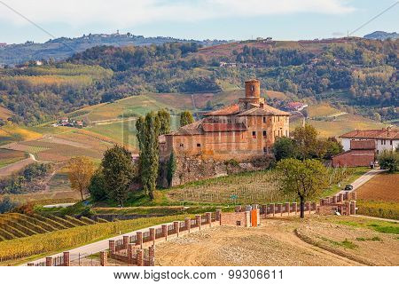 Autumnal vineyards and Castello della Volta in Piedmont, Northern Italy.