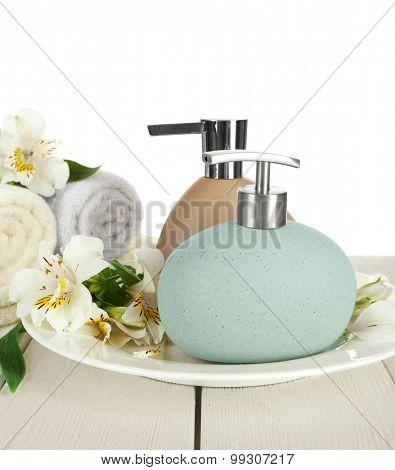 Soft towels with dispenser and flowers isolated on white