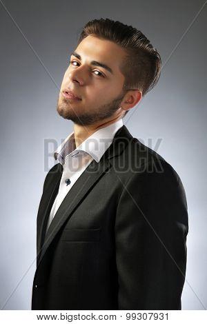Handsome businessman on gray background