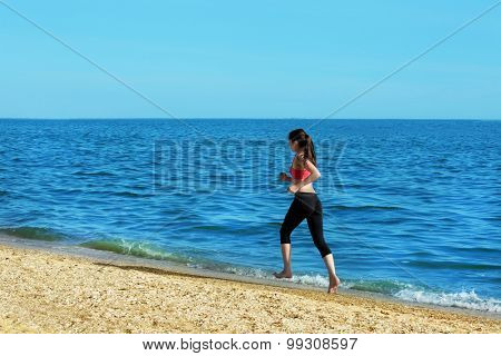 Young woman jogging on beach