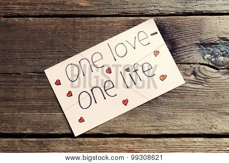 Written message on piece of paper on wooden table close up